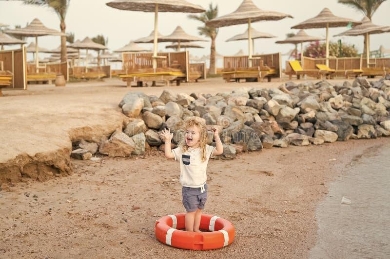 Kleines Baby mit glücklichem Gesicht mit Rettungsgürtel auf Strand stockfotos