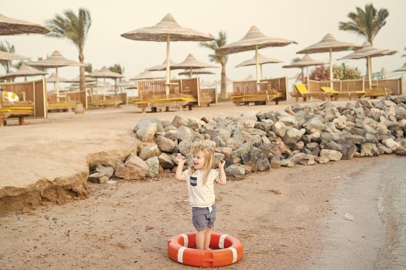 Kleines Baby mit glücklichem Gesicht mit Rettungsgürtel auf Strand stockbilder