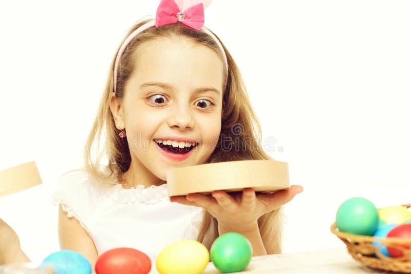 Kleines Baby oder nettes Kind mit den glücklichen rosa Ohren des Gesichtes und des Kaninchens auf blondem Kopf um bunte Ostereiho stockbilder