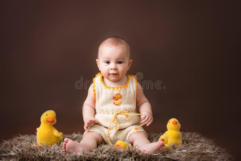 Kleines Baby, spielend mit dekorativen Enten, auf Braue lizenzfreie stockbilder