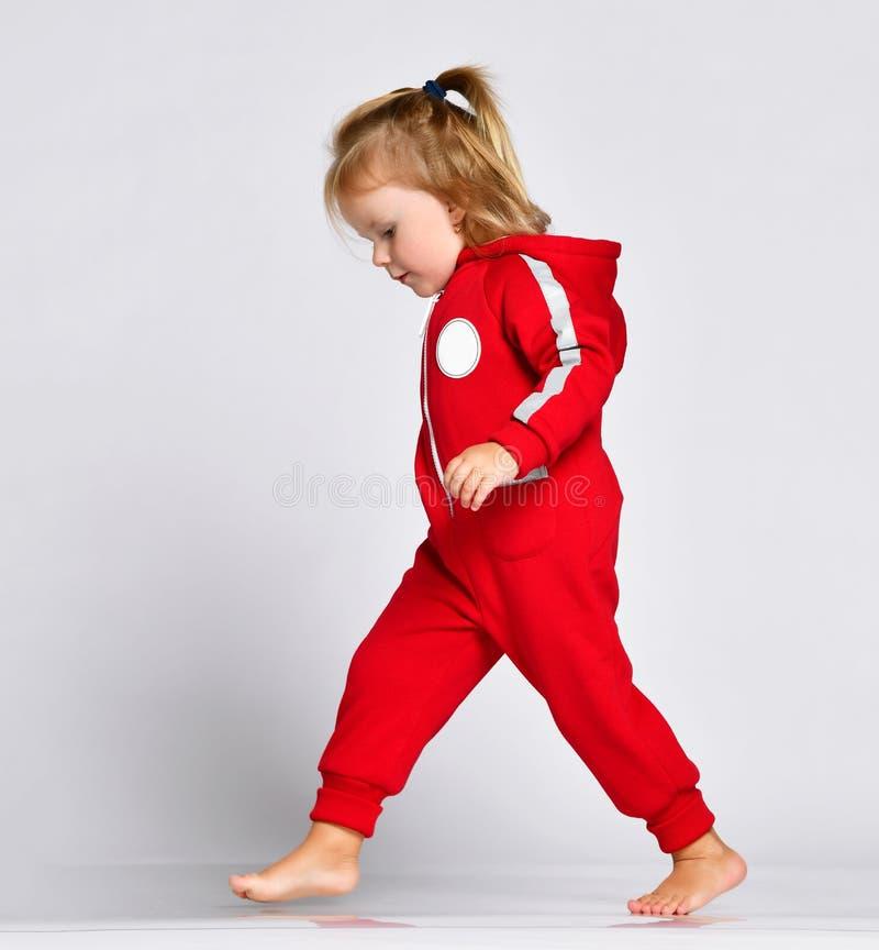 Kleines Babykleinkind, das erste Schritte im roten Stoff auf Grau machend geht stockfotos