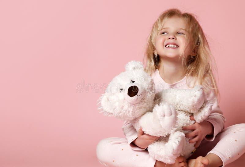 Kleines Babykleinkind, das mit dem glücklichen Lächeln des weißen polaren Teddybären auf Rosa sitzt lizenzfreies stockbild