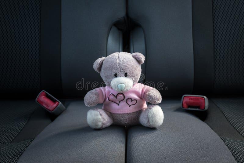 Kleines befestigtes Sitzen des Teddybären nicht auf einem Autositz lizenzfreie stockfotografie