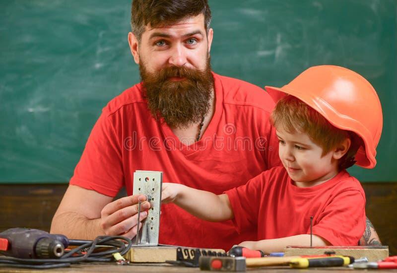 Kleines behilfliches Konzept Junge, das Kind, das im Schutzhelm beschäftigt ist, macht eigenhändig und repariert mit Vati Vater m stockfotografie