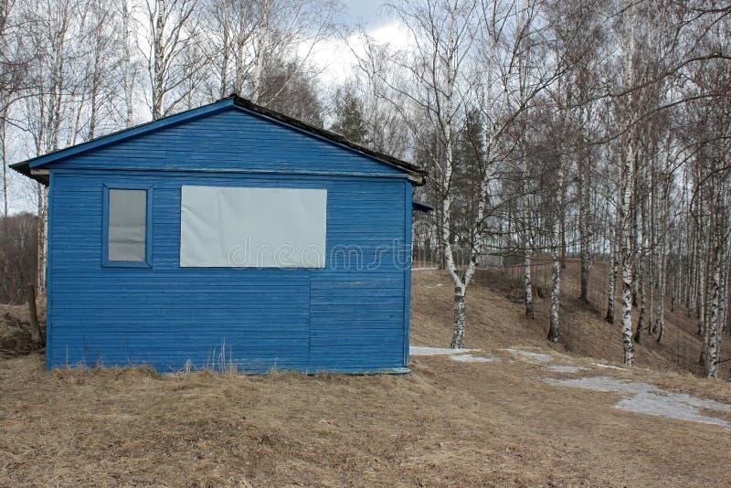 Kleines blaues Haus auf trockenem Gras lizenzfreies stockbild