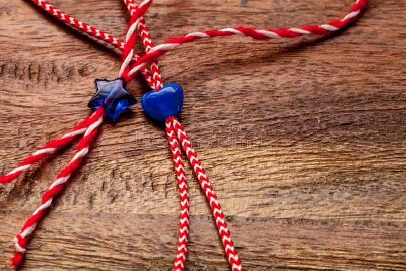 Kleines blaues Herz und Stern auf den roten und weißen Bäckern twine mit hölzernem Hintergrund/internationalem Frauen ` s Tagesko stockfotos