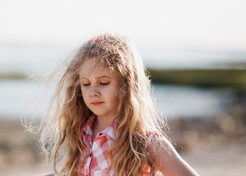 Kleines blondes Kindermädchen, das in Sommerstrand bei Sonnenuntergang geht stockfoto