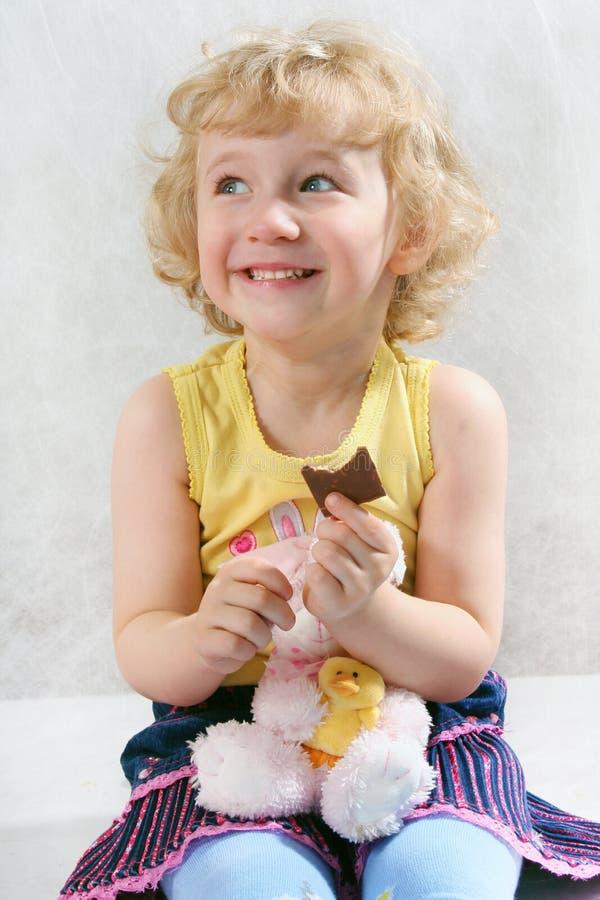 Kleines blondes lockiges Mädchen, das Schokolade mit Spielzeug isst stockfotos