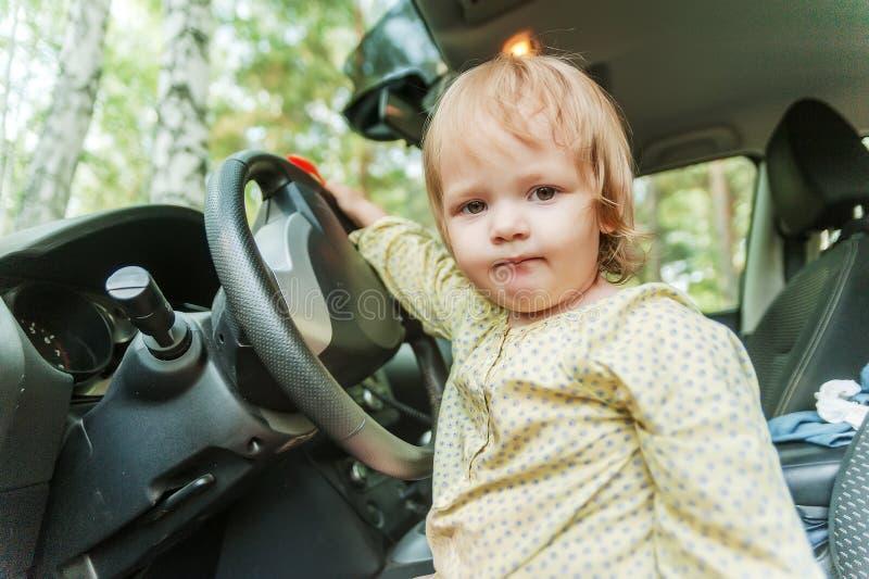 Kleines blondes Mädchen, das Auto fährt stockbild