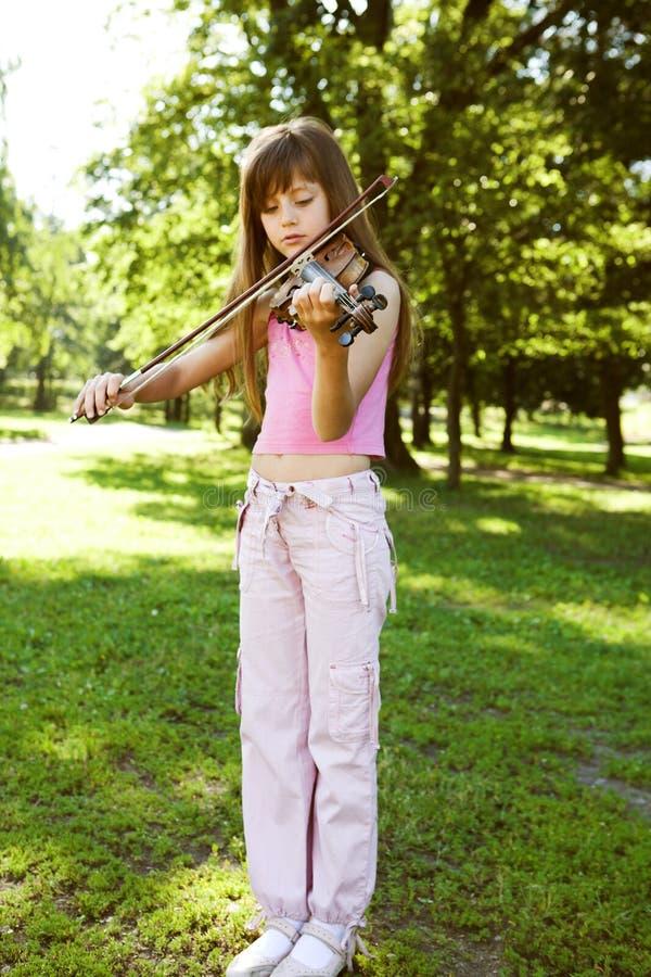Kleines blondes Mädchen, das im Park spielt stockfoto