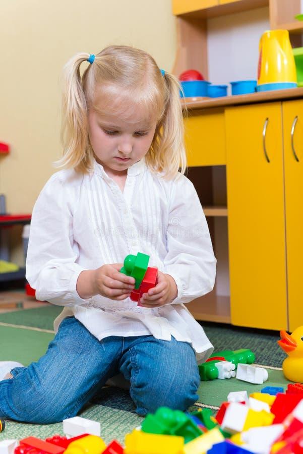 Kleines blondes Mädchen, das mit Mauerziegeln in der Vorschule spielt stockbild