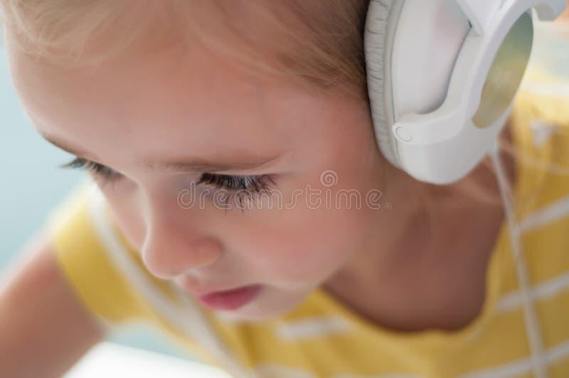 Kleines blondes Mädchen in den Kopfhörern stockfoto
