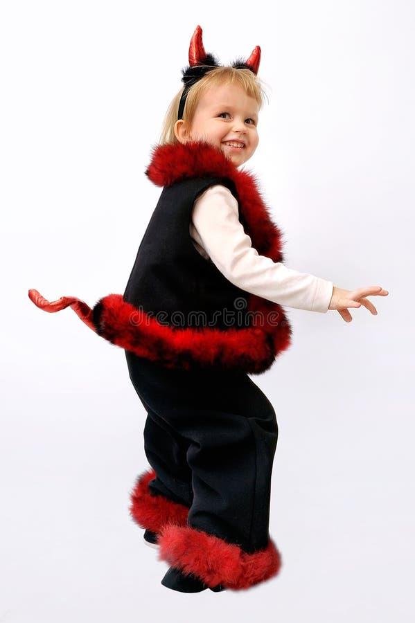 Kleines blondes Mädchen, gekleidet in einem Teufel auf Karneval lizenzfreie stockfotos