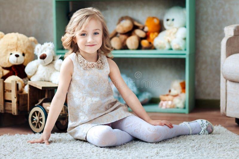 Kleines blondes Mädchen im weißen Kleid sitzt in Kind-` s Raum mit Spielwaren stockfotografie
