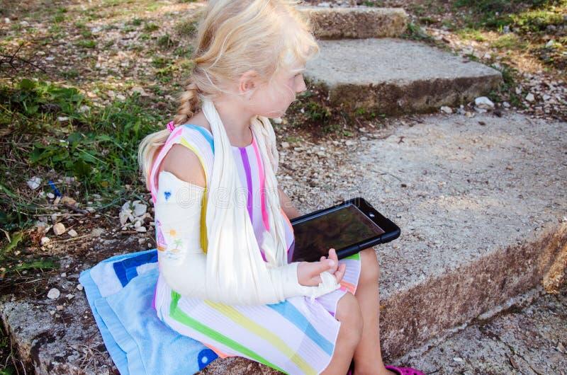 Kleines blondes Mädchen mit dem Handbruch stockbilder
