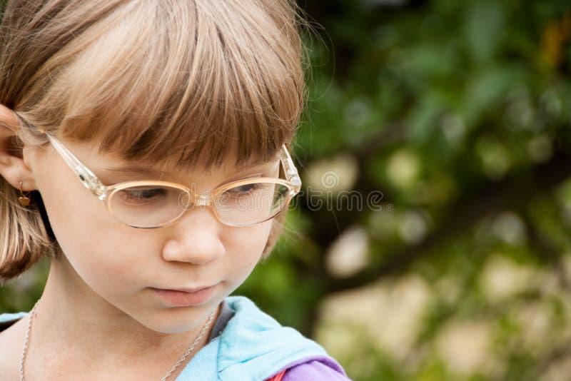 Kleines blondes Mädchen mit Gläsern stockbild