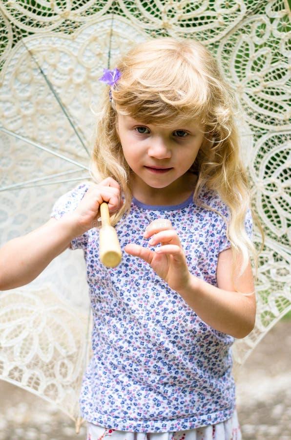 Kleines blondes Mädchen mit Regenschirm stockfoto