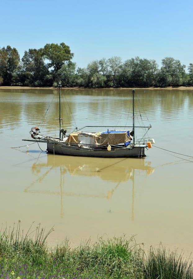 Kleines Boot auf dem Guadalquivir-Fluss, wie er durch Lederhäute del Provinz Rios, Sevilla überschreitet, Andalusien, Spanien lizenzfreie stockbilder