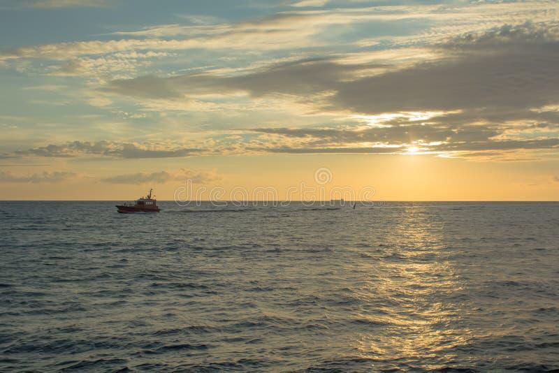 Kleines Boot auf dem hellen Gehen des Sonnenuntergangs zu tragen stockbild