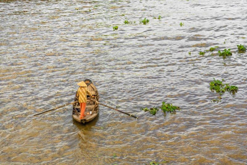 Kleines Boot, das Leute transportiert, dem sich hin- und herbewegenden Markt im Mekong, Vietnam zur?ck zu zu gehen stockfoto