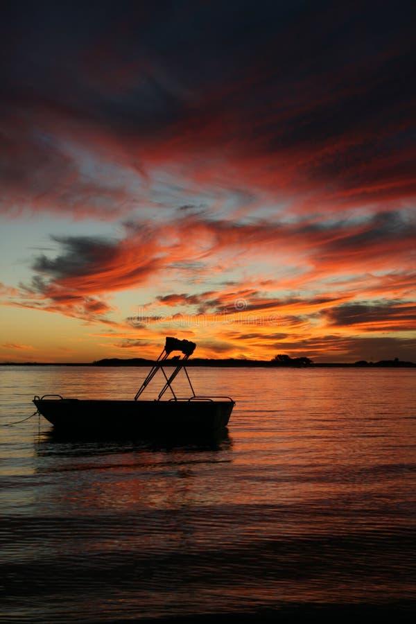 Kleines Boot im Wassersonnenuntergang lizenzfreie stockbilder
