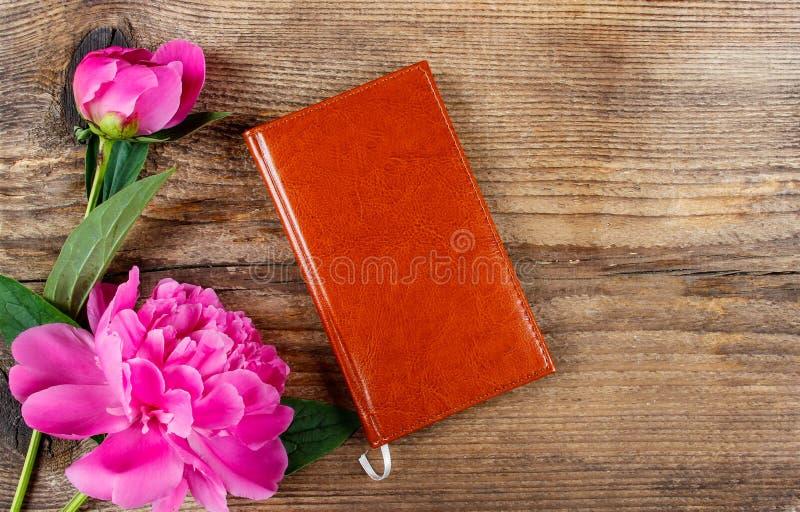 Kleines Buch und üppige rosa Pfingstrosen auf Holztisch lizenzfreie stockfotografie