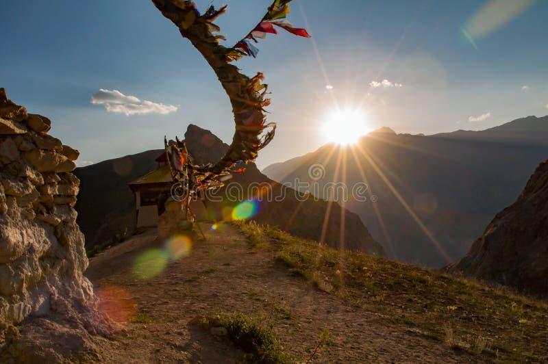 Kleines buddhistisches Kloster mit Gebetsflaggen und -sonne strahlt während des Sonnenuntergangs aus stockbild