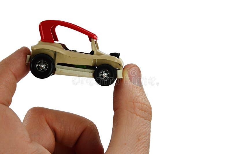 Kleines Buggyauto-Spielzeugmodell mit rotem Dach hielt zwischen Daumen und Zeigefinger der erwachsenen Person, weißer Hintergrund stockfotos