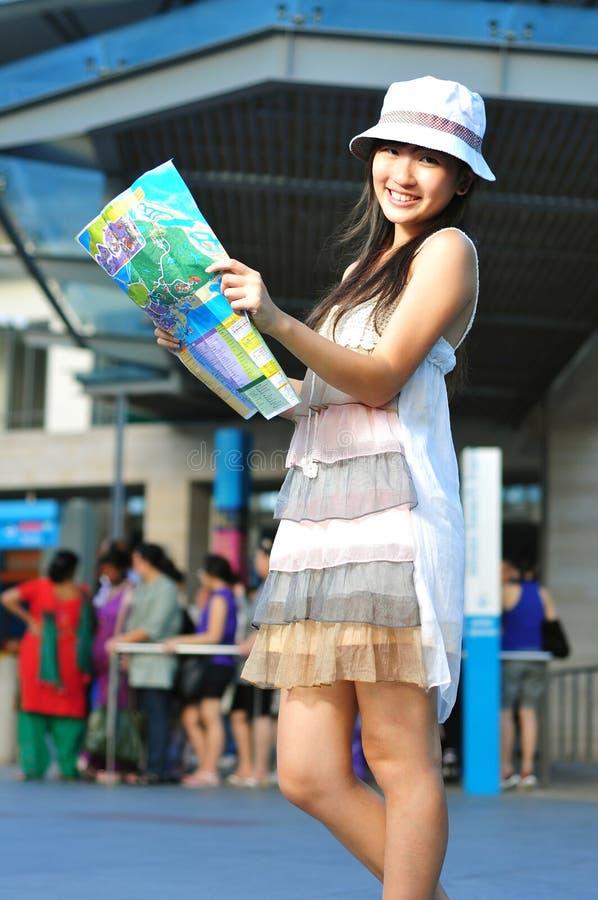 Kleines chinesisches asiatisches touristisches Mädchen, das ihre Karte verwendet stockfotografie