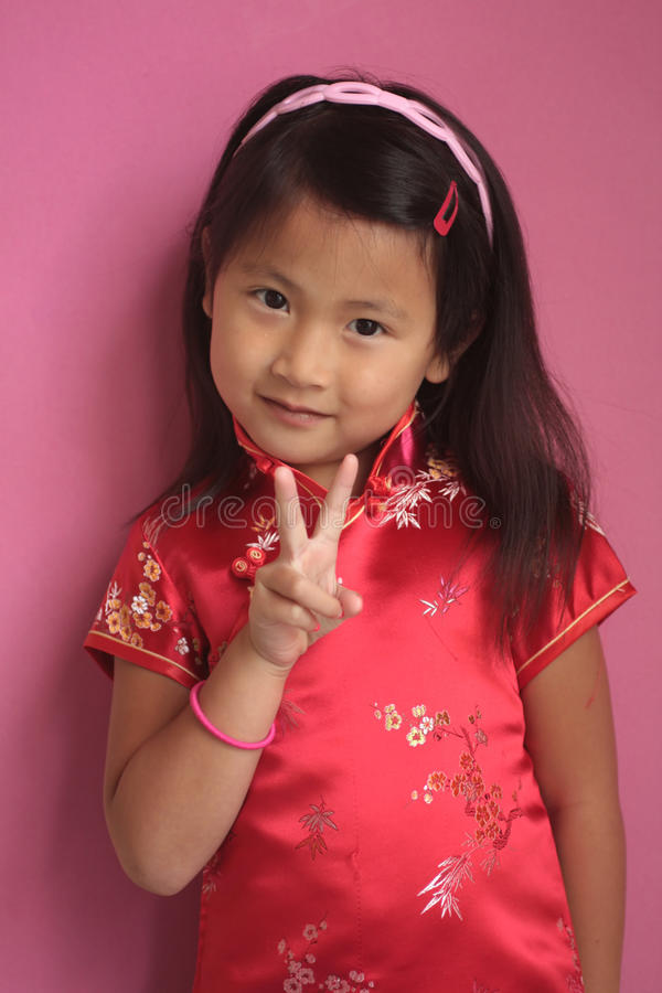 Kleines chinesisches Mädchen mit rotem Kleid stockbilder