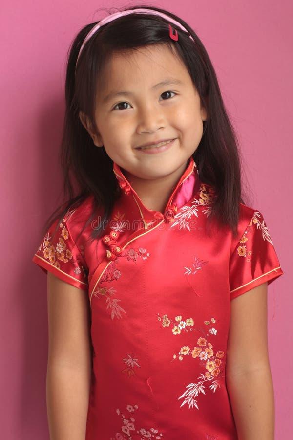 Kleines chinesisches Mädchen mit rotem Kleid stockfotografie