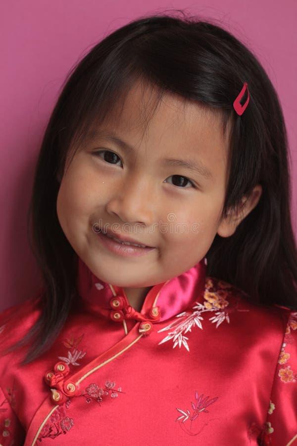 Kleines chinesisches Mädchen mit rotem Kleid lizenzfreie stockbilder