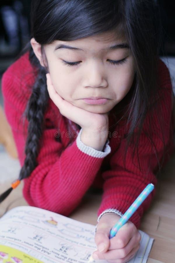 Kleines die Stirn runzelndes Mädchen beim Handeln von Heimarbeit stockbild