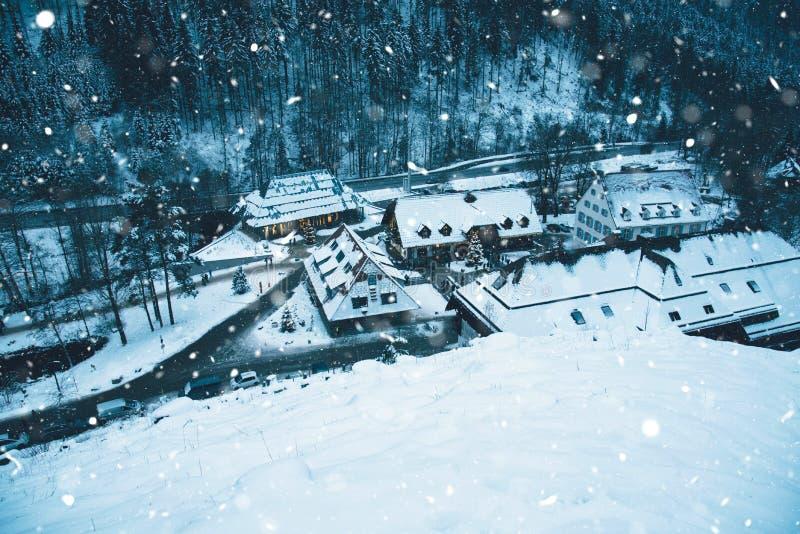 Kleines Dorf in den schneebedeckten Bergen nachts Winter lizenzfreie stockbilder