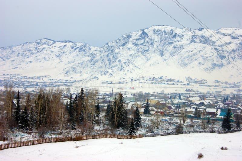 Kleines Dorf im Hintergrund der Wintergebirge stockfotos