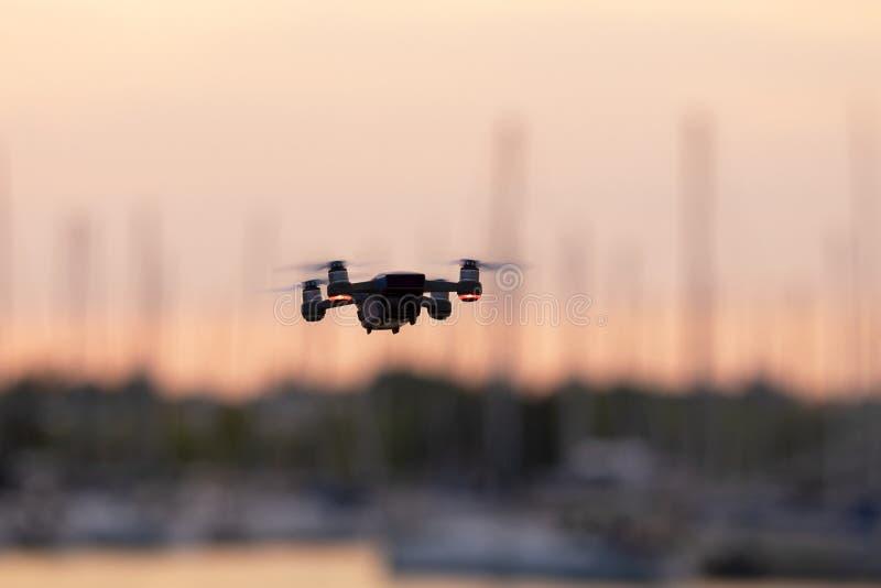 Kleines Drohnenfliegen, das in der Luft mit Sonnenunterganghimmel im Hintergrund hängt stockbilder