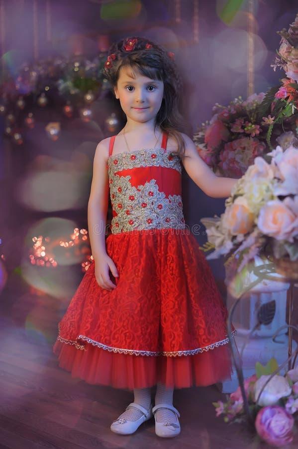 Kleines dunkelhaariges Mädchen in einem roten Kleid nahe bei den Blumen in einem Vase lizenzfreies stockbild