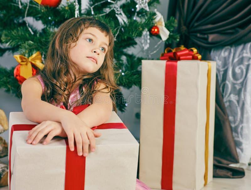 Kleines durchdachtes Mädchen träumt nahe einem Weihnachtsbaum, der eine große Geschenkbox hält stockfotografie
