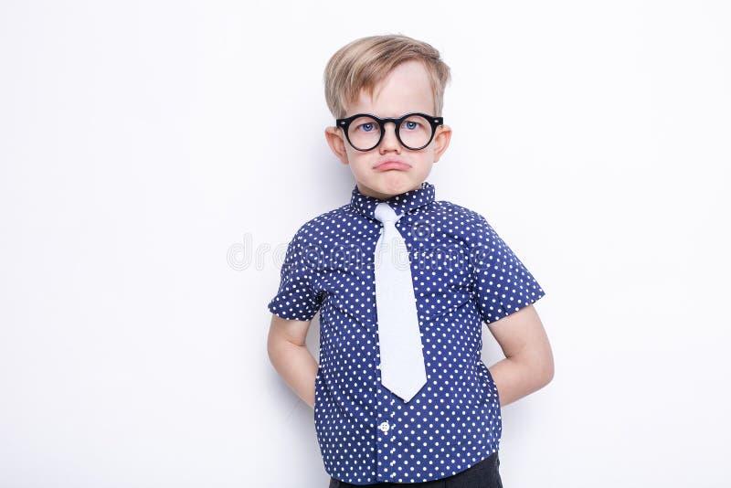 Kleines entzückendes Kind in der Bindung und in den Gläsern schule vortraining Art und Weise Studioporträt lokalisiert über weiße stockbild