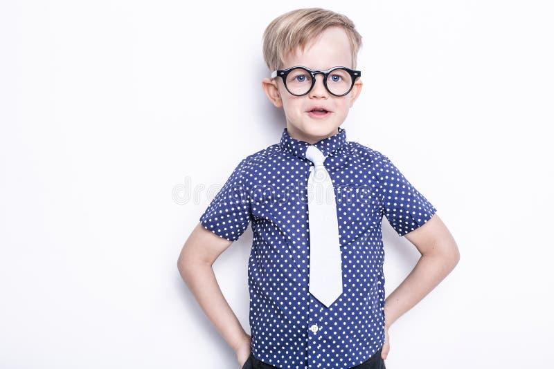 Kleines entzückendes Kind in der Bindung und in den Gläsern schule vortraining Art und Weise Studioporträt lokalisiert über weiße stockfotos