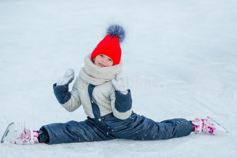 Kleines entzückendes Mädchen, das auf Eis mit Rochen nach Fall sitzt stockfoto