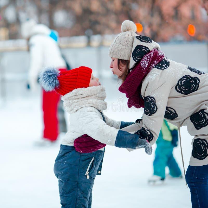 Kleines entzückendes Mädchen, das auf Eisbahn mit Mutter eisläuft stockfotografie