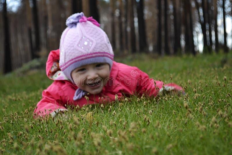 Kleines entzückendes Mädchen, das auf Gras liegt lizenzfreie stockbilder