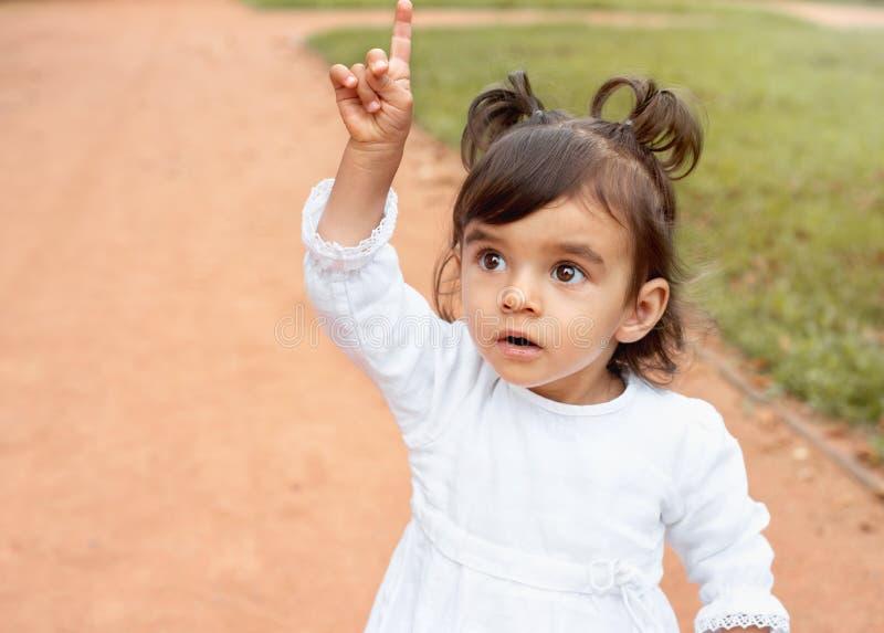 Kleines erstaunliches Mädchen, das mit dem Finger in den Park zeigt lizenzfreies stockbild