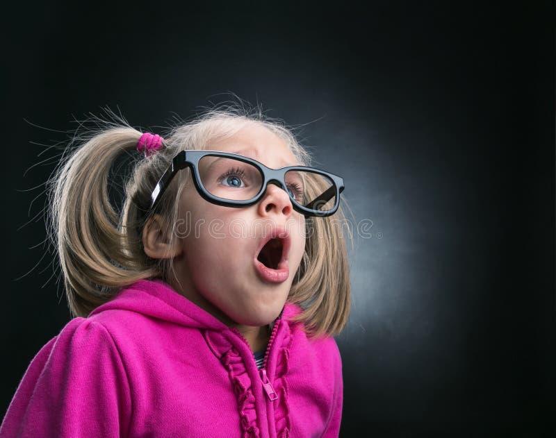 Kleines erstauntes Mädchen in den lustigen großen Schauspielen stockfoto