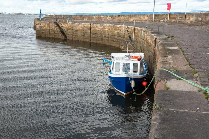 Kleines Fischerboot im Hafen und im bew?lkten Himmel lizenzfreie stockbilder