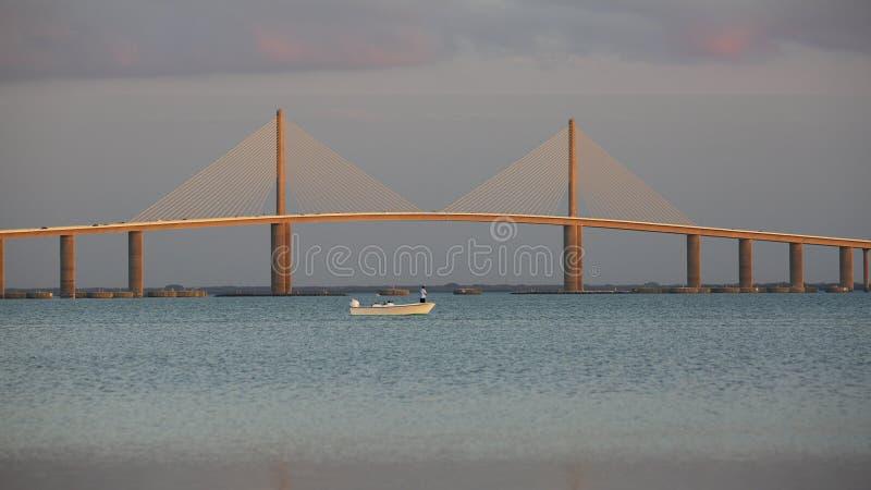 Kleines Fischerboot unter der Sonnenschein Skyway-Brücke - Florida stockfotografie