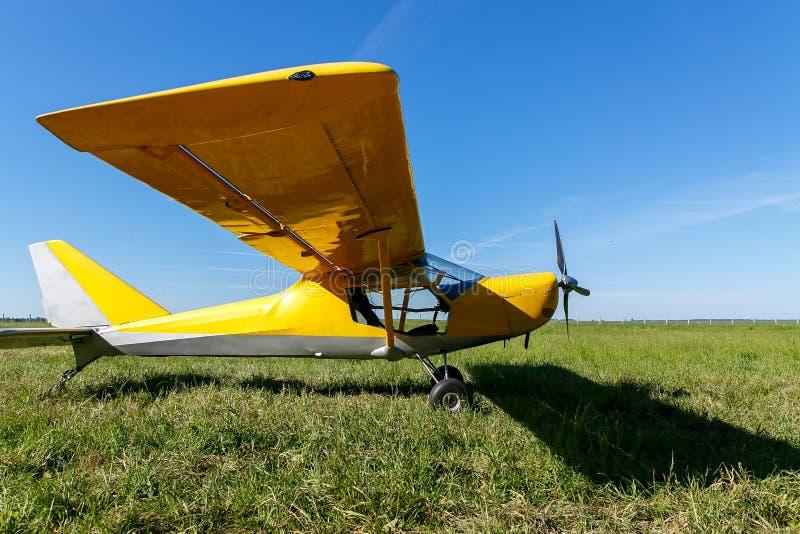 kleines Flugzeug, das auf Feld, gelbe Fläche auf dem Gras wartet stockbild