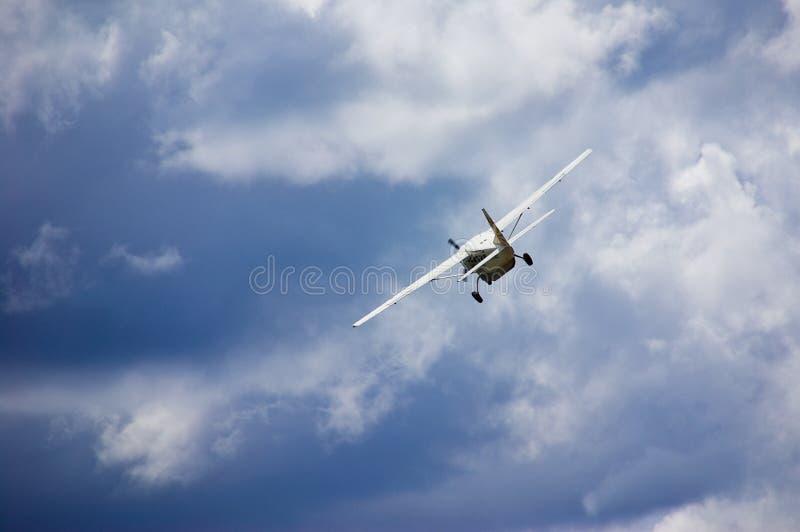 Kleines Flugzeug im blauen bewölkten Himmel lizenzfreie stockbilder