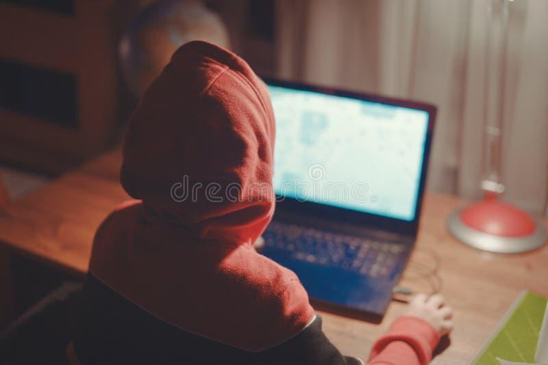 Kleines Gamerkind in der Haube, die das Massenmultispielerspiel on-line auf Laptop spielt lizenzfreie stockfotos